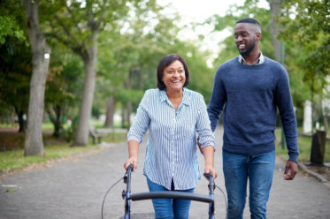 Cheerful senior man lying on bed receiving health care at home